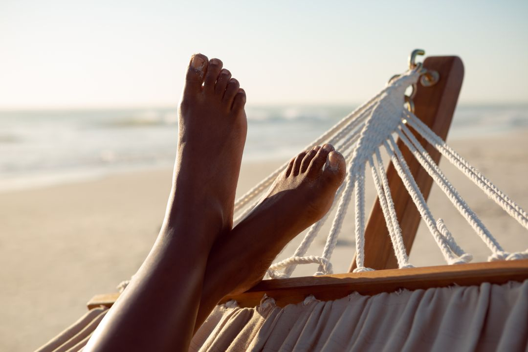 Low section of woman relaxing with feet up in a hammock on the beach