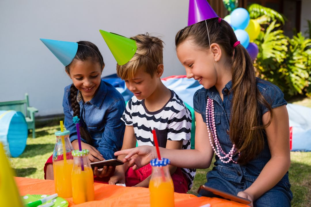 Happy children using mobile phone while sitting at table during birthday party Free Stock Images from PikWizard