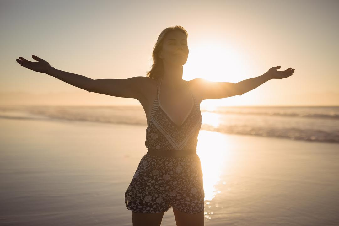 Young woman with arms outstretched standing at beach during dusk