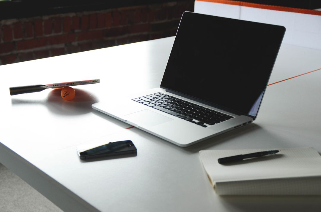 Image of a laptop on a desk with notebook and pen