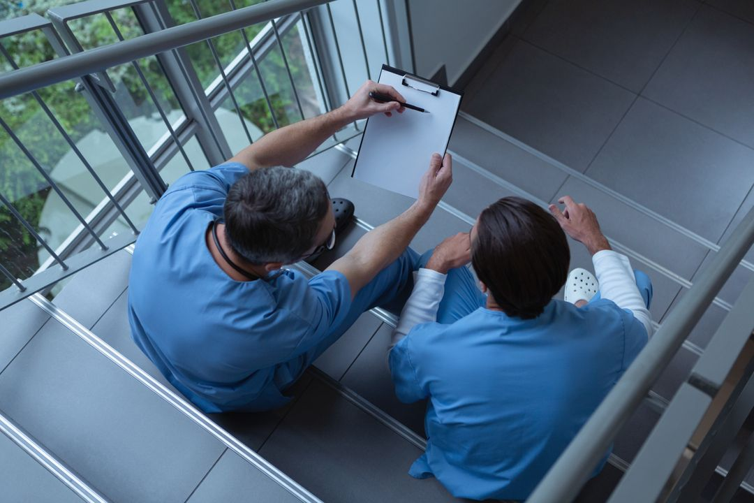 High angle view of male surgeons discussing over clipboard while sitting on stairs at hospital Free Stock Images from PikWizard
