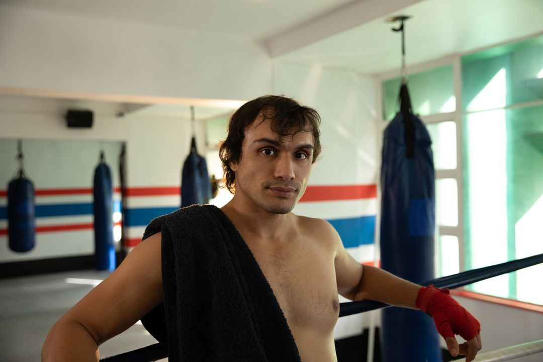 Front view of a young mixed race male boxer with short dark hair, shirtless, with towel over his shoulder, standing in a boxing gym, looking straight to the camera.