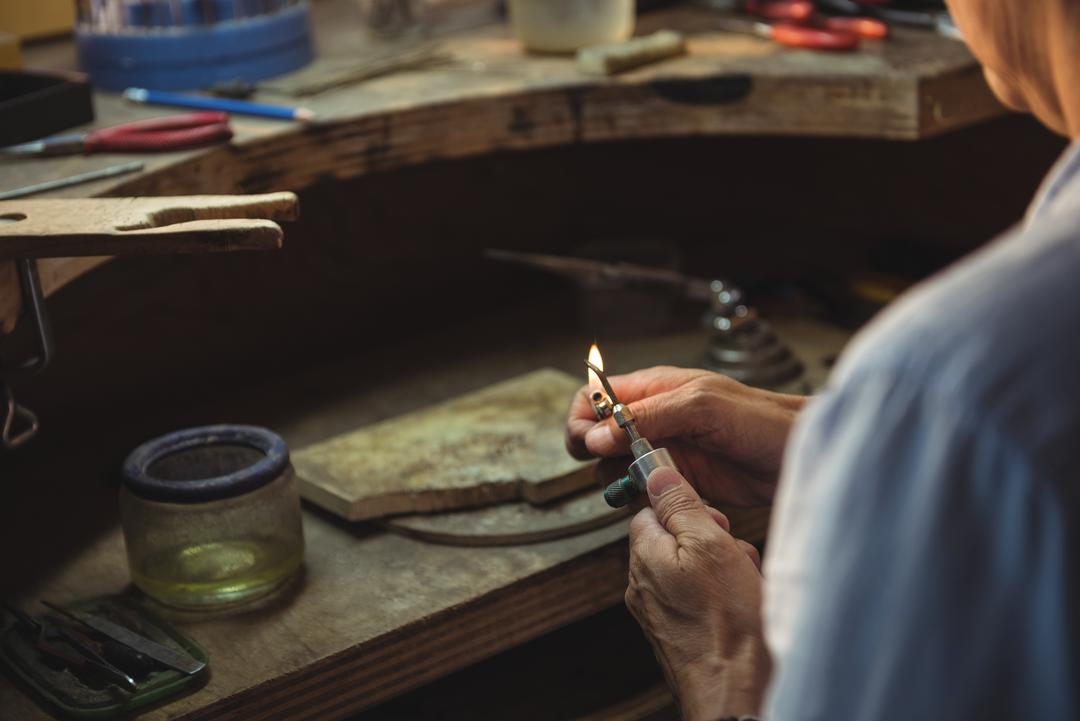 Craftswoman lighting blow torch in workshop Free Stock Images from PikWizard