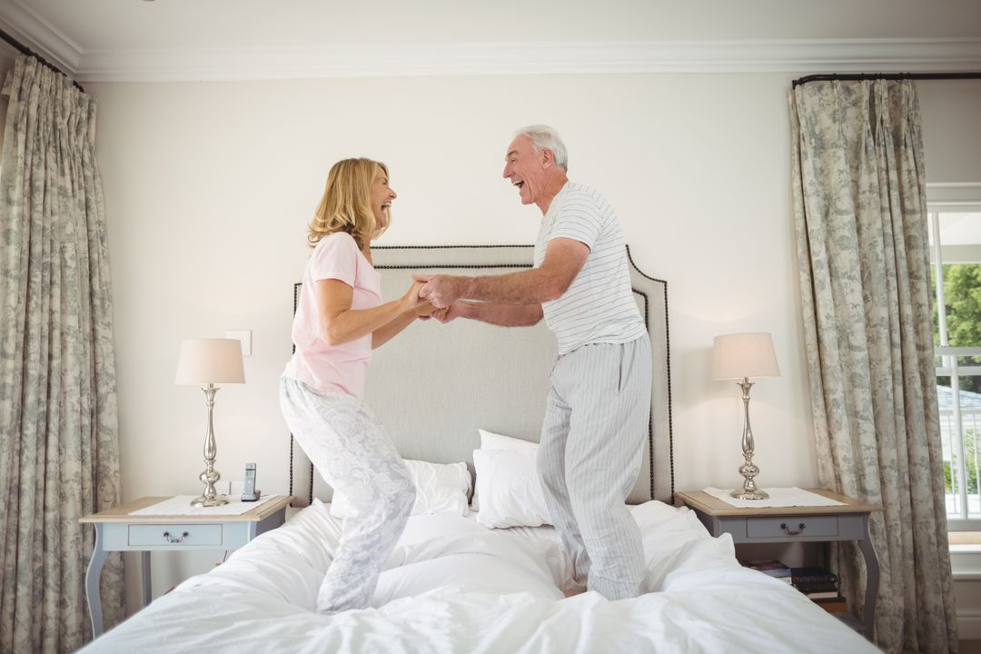 Happy senior couple dancing on bed in bedroom Free Stock Images from PikWizard
