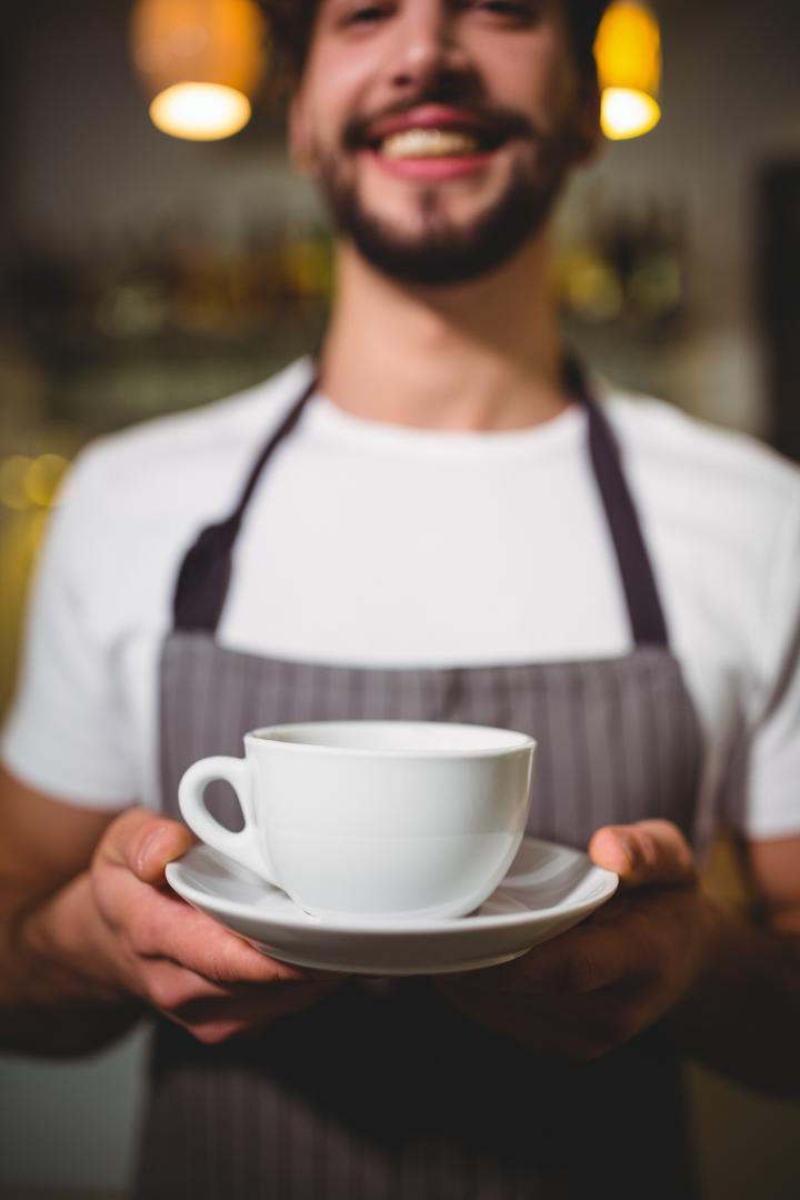 Portrait of waiter holding cup of coffee in café