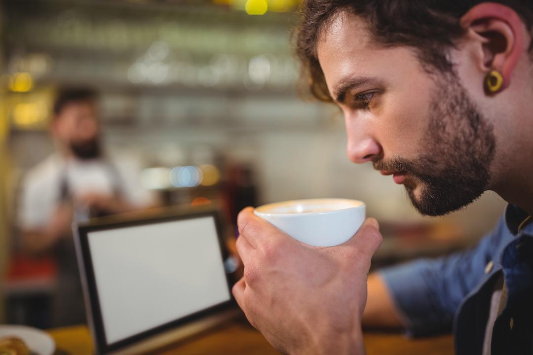 Man sitting at counter and using digital tablet while having coffee in café