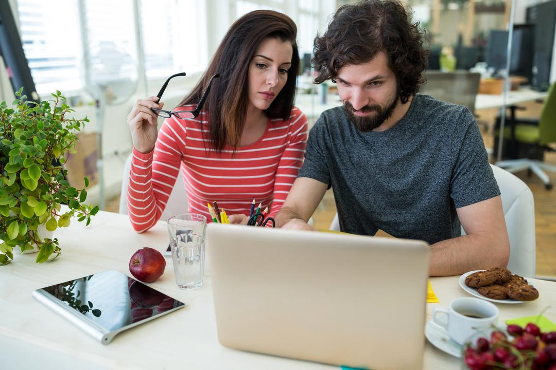 Male and female graphic designers using laptop in office