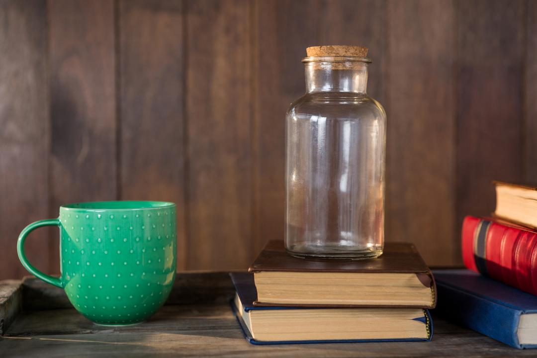 Close-up of jar, books and mug on wooden table