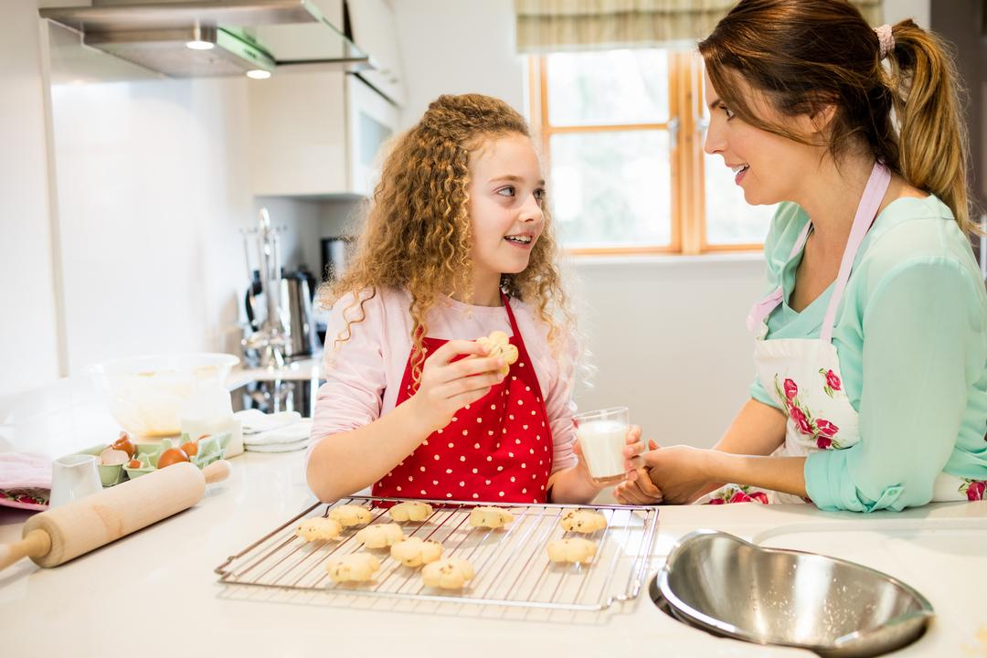 Daughter interacting with mother while having cookies in the kitchen at home Free Stock Images from PikWizard