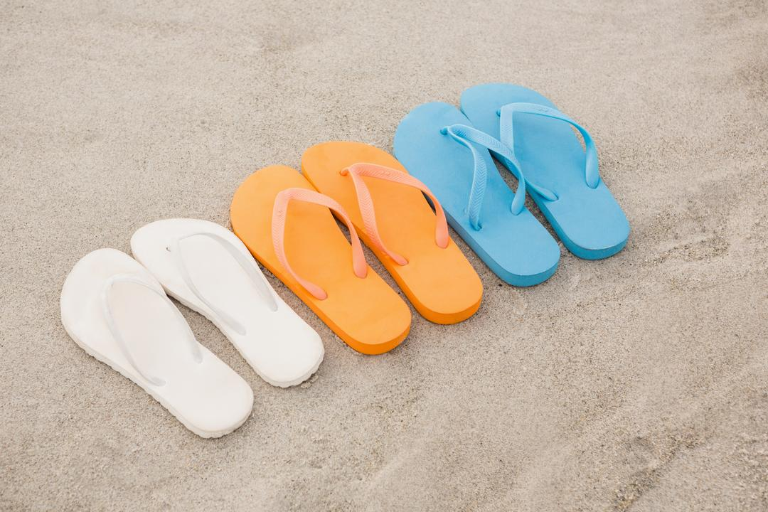 Multi-color flip flops arranged in a row in sand at beach Free Stock Images from PikWizard