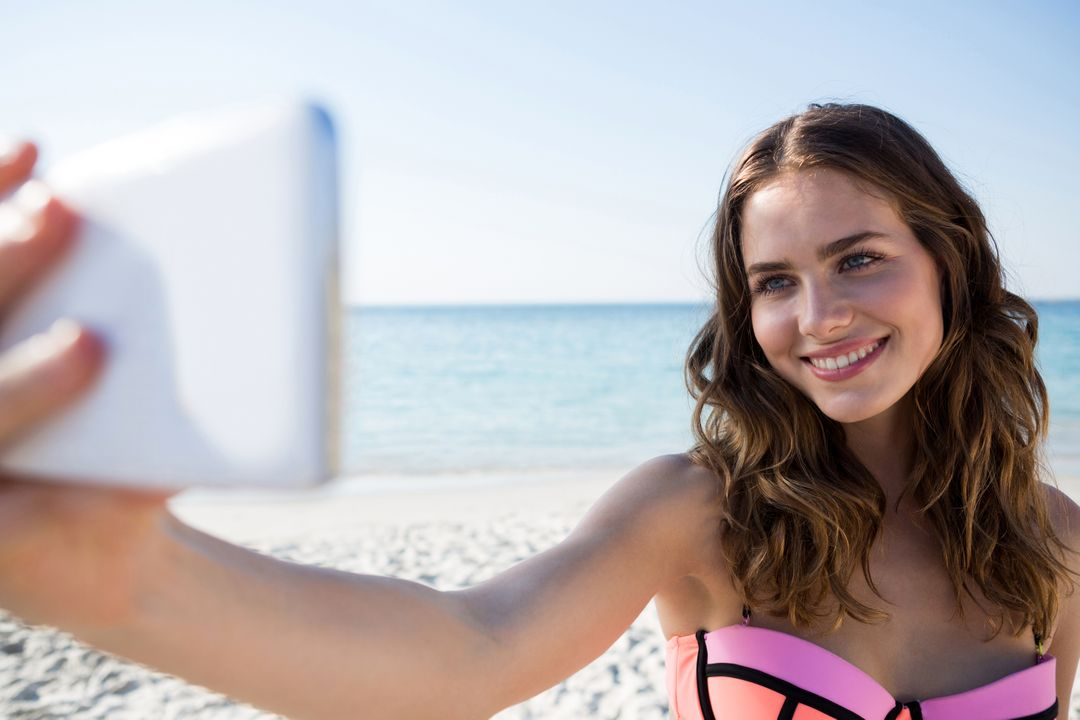 Happy young woman wearing bikini while taking selfie at beach on sunny day Free Stock Images from PikWizard