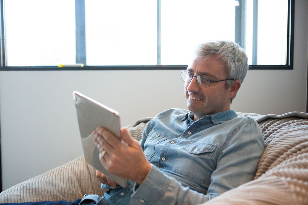 Side of a happy senior Caucasian man working in a creative office, sitting on a armchair, using a digital tablet, smiling