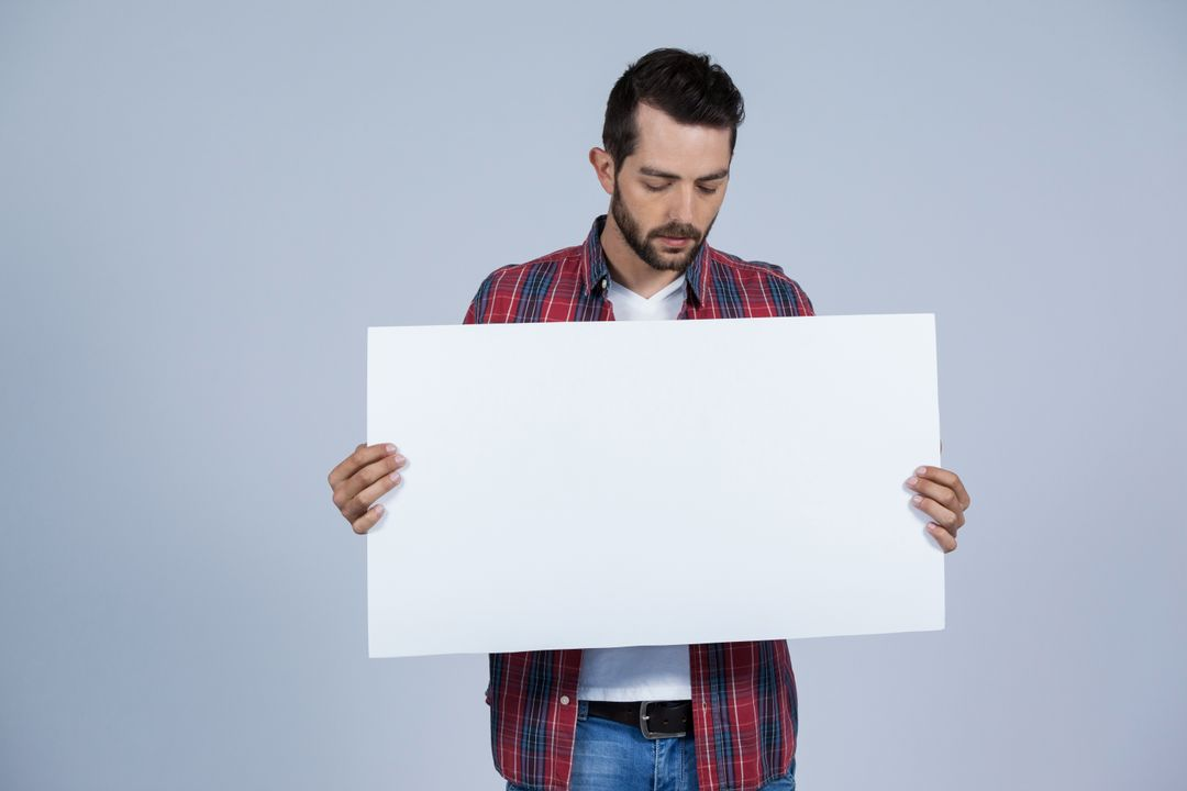 Man holding a blank placard against grey background Free Stock Images from PikWizard