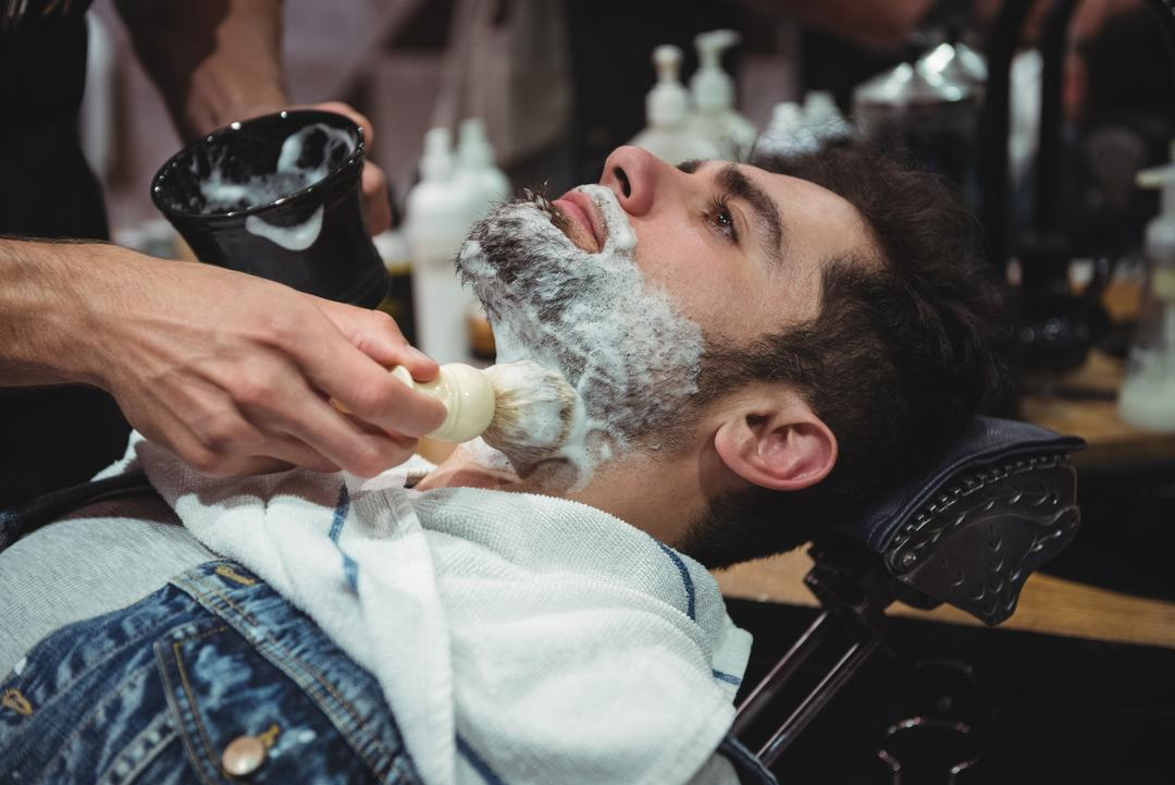 Mid section of barber applying cream on clients beard in baber shop