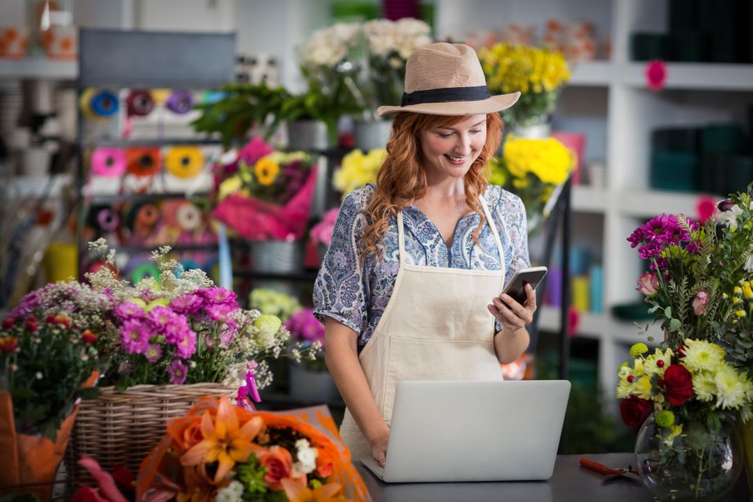 Female florist using mobile phone while using laptop in flower shop Free Stock Images from PikWizard