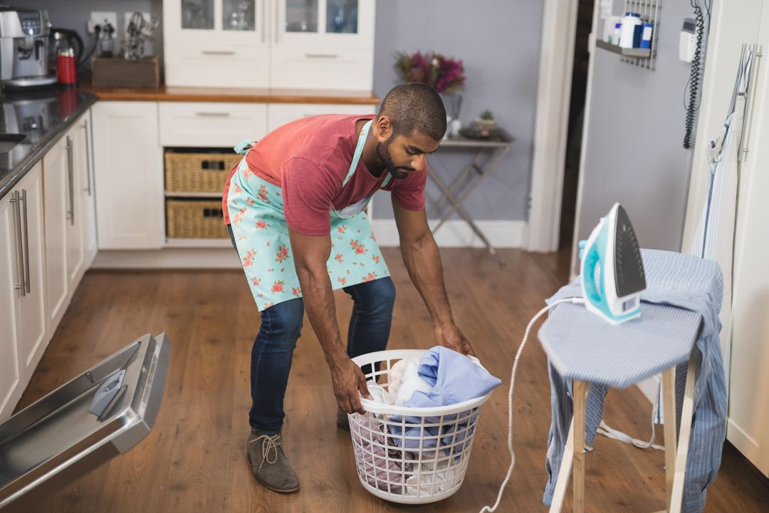 Full length of young man lifting laundry basket by ironing board in kitchen at home Free Stock Images from PikWizard