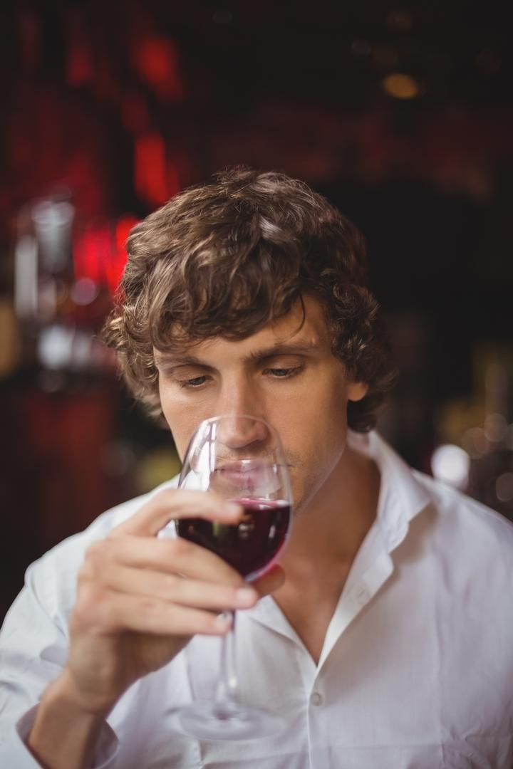Man having a glass of red wine at bar