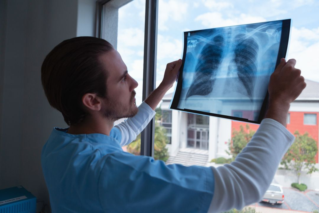 Side view of male surgeon examining x ray in clinic at hospital