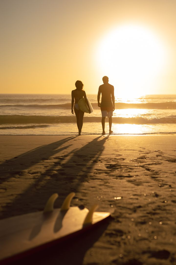 Rear view of couple walking together with surfboard on the beach