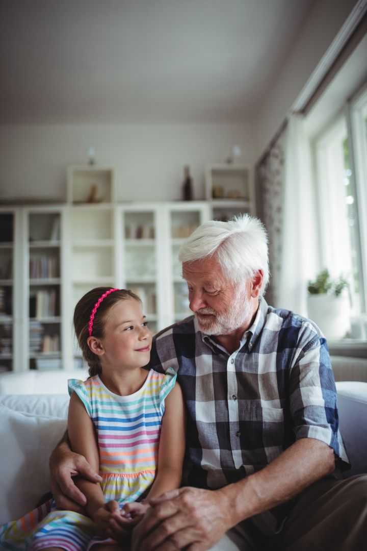 Senior man sitting with his granddaughter at home Free Stock Images from PikWizard