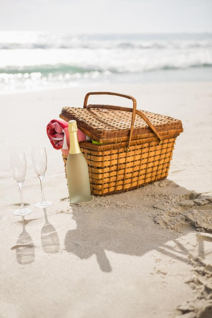 Picnic basket, champagne bottle and two glasses at tropical sand beach