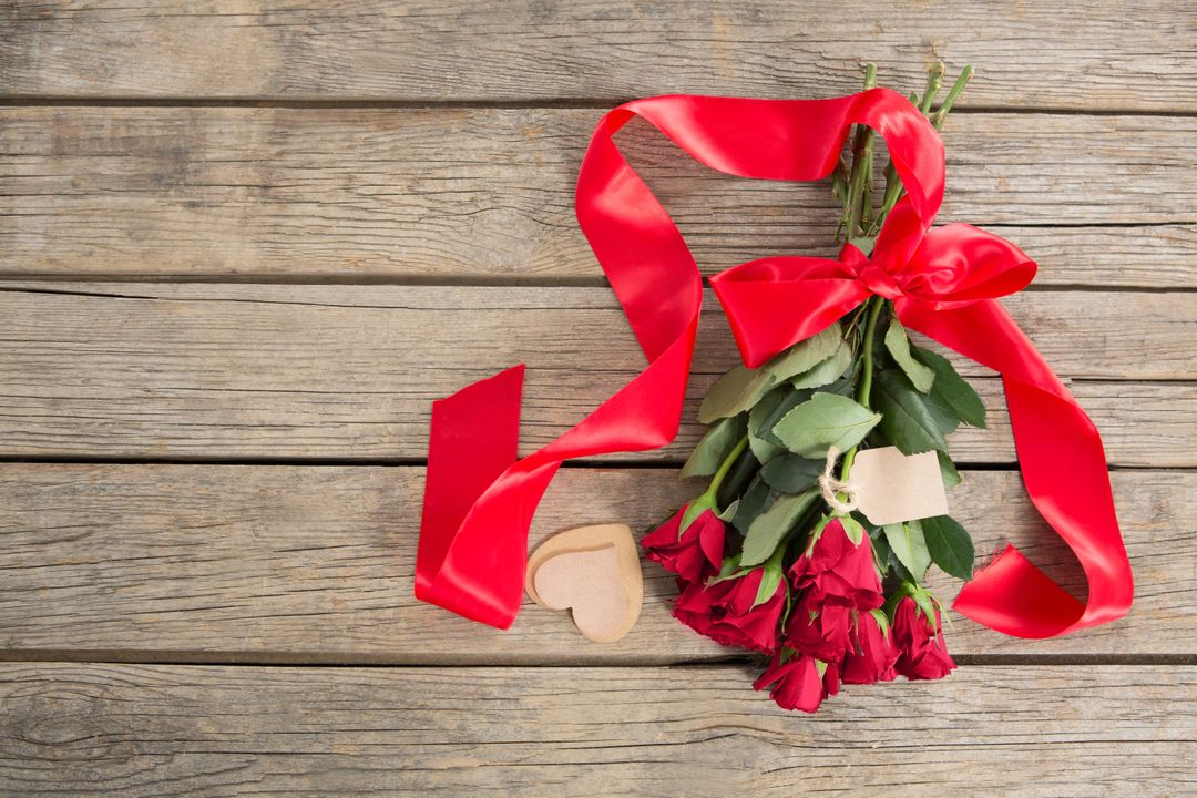 Bunch of red roses surrounded with heart shape decoration on wooden background Free Stock Images from PikWizard