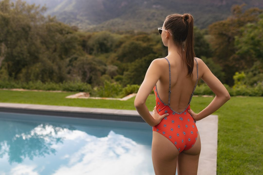Rear view of Caucasian woman in swimwear standing with hands on hip near poolside in the backyard