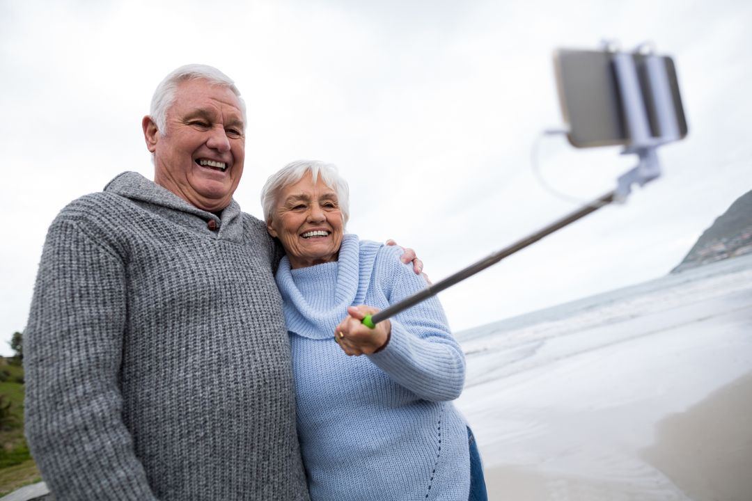 Senior couple taking a selfie from selfie stick on beach Free Stock Images from PikWizard