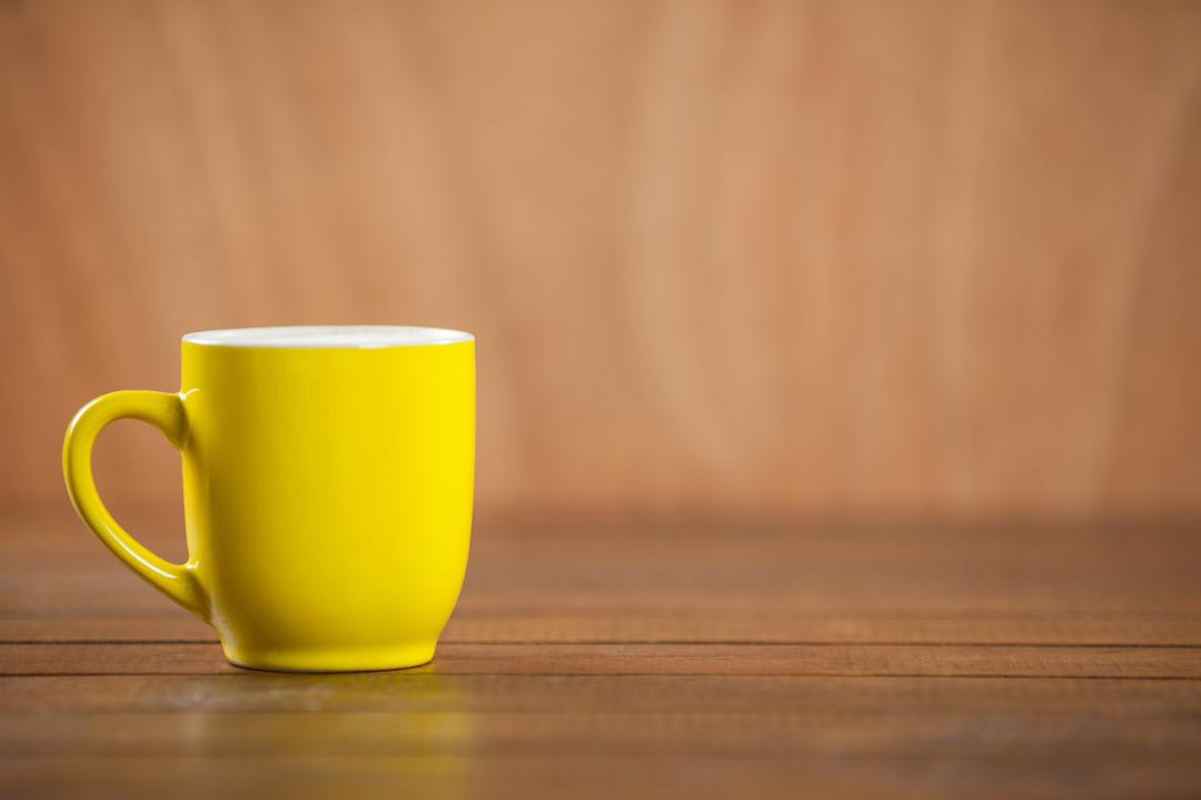 Yellow coffee mug on wooden table over brown background Free Stock Images from PikWizard