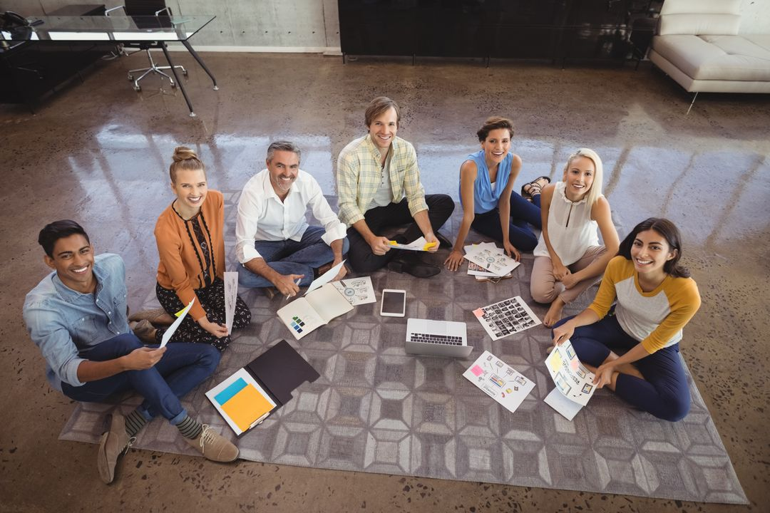 Portrait of creative business team sitting on floor in office Free Stock Images from PikWizard