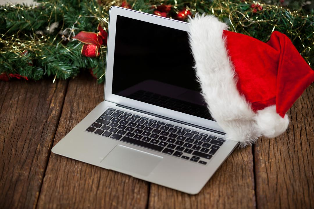 Laptop with santa hat on a plank