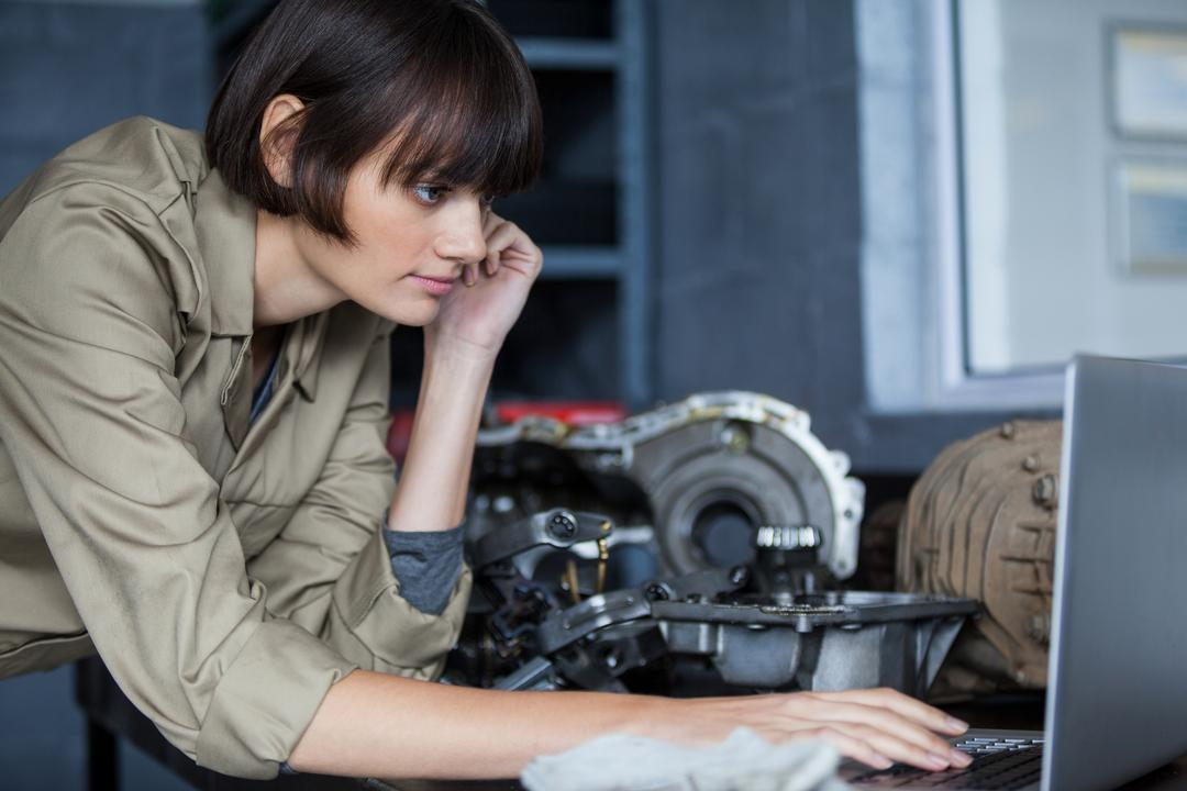 Female mechanic leaning on table and using laptop at the repair garage