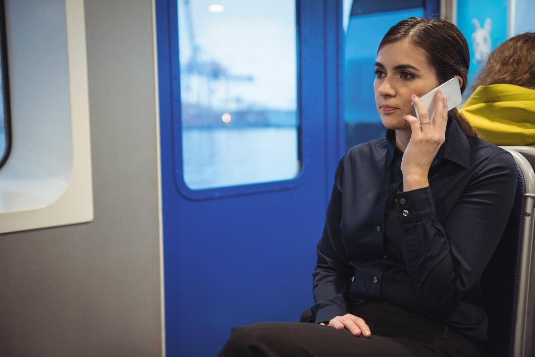 Beautiful businesswoman talking on phone while sitting in train