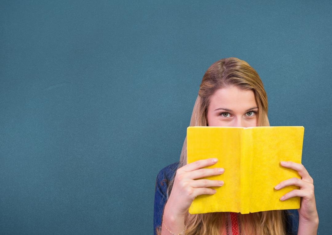 Woman holding a book in front of her face against blue background