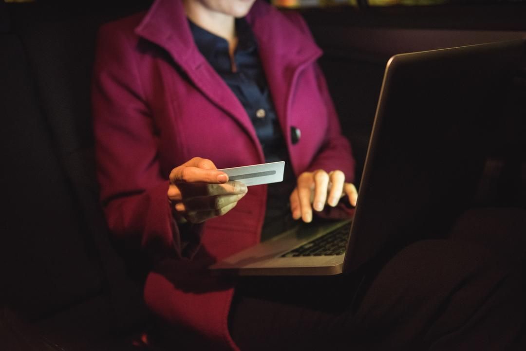 Businesswoman doing online shopping on laptop with credit card in car Free Stock Images from PikWizard