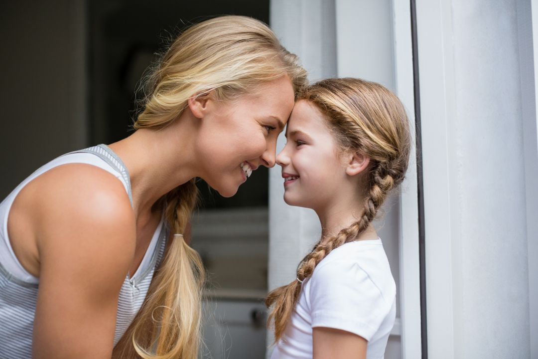 Smiling mother and daughter looking face to face at home Free Stock Images from PikWizard