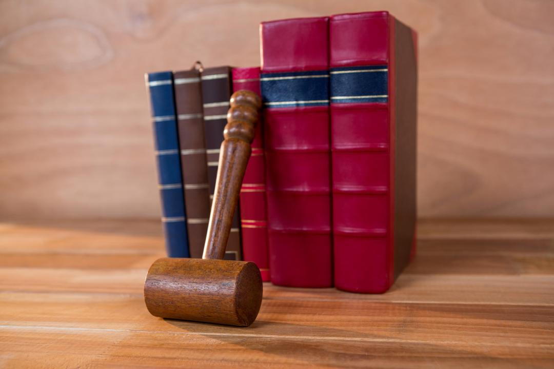 A judge's gavel in front of a selection of law books on a wooden background