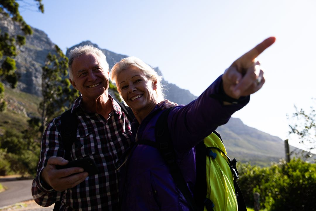 Front view of a senior Caucasian couple enjoying time in nature together, taking a break, using a smartphone together, a woman is pointing at something Free Stock Images from PikWizard