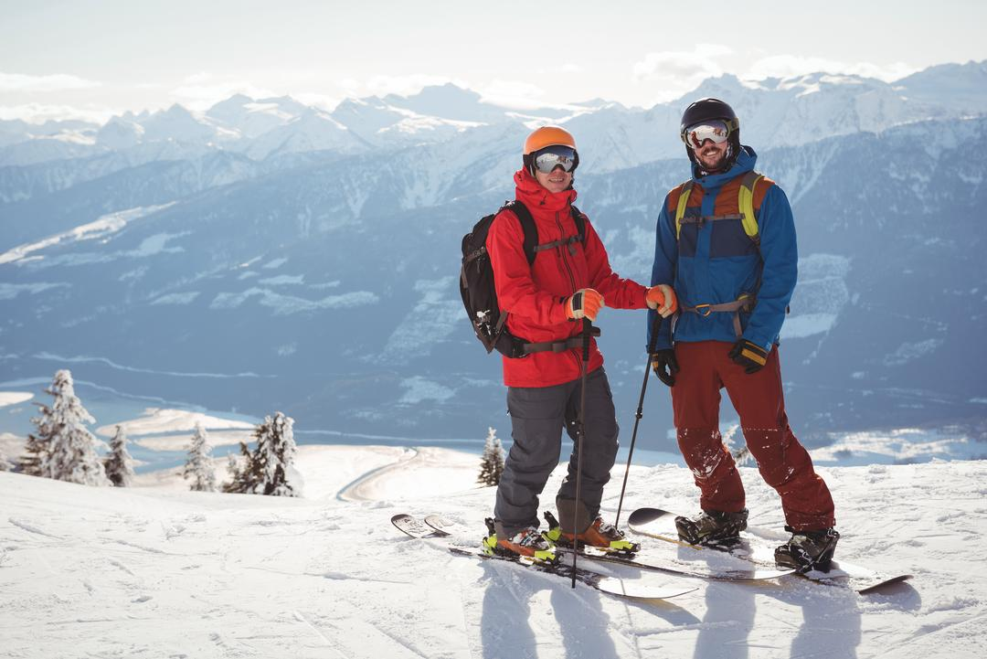 Two skiers standing together on snow covered mountain during winter