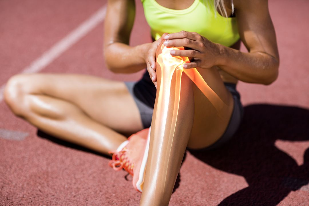 Low section of female athlete suffering from knee pain while sitting on track during sunny day