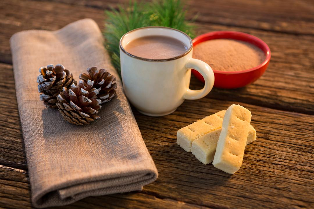 Pine cone, coffee cup, coffee powder, sweet food, and christmas fir with napkin on wooden plank