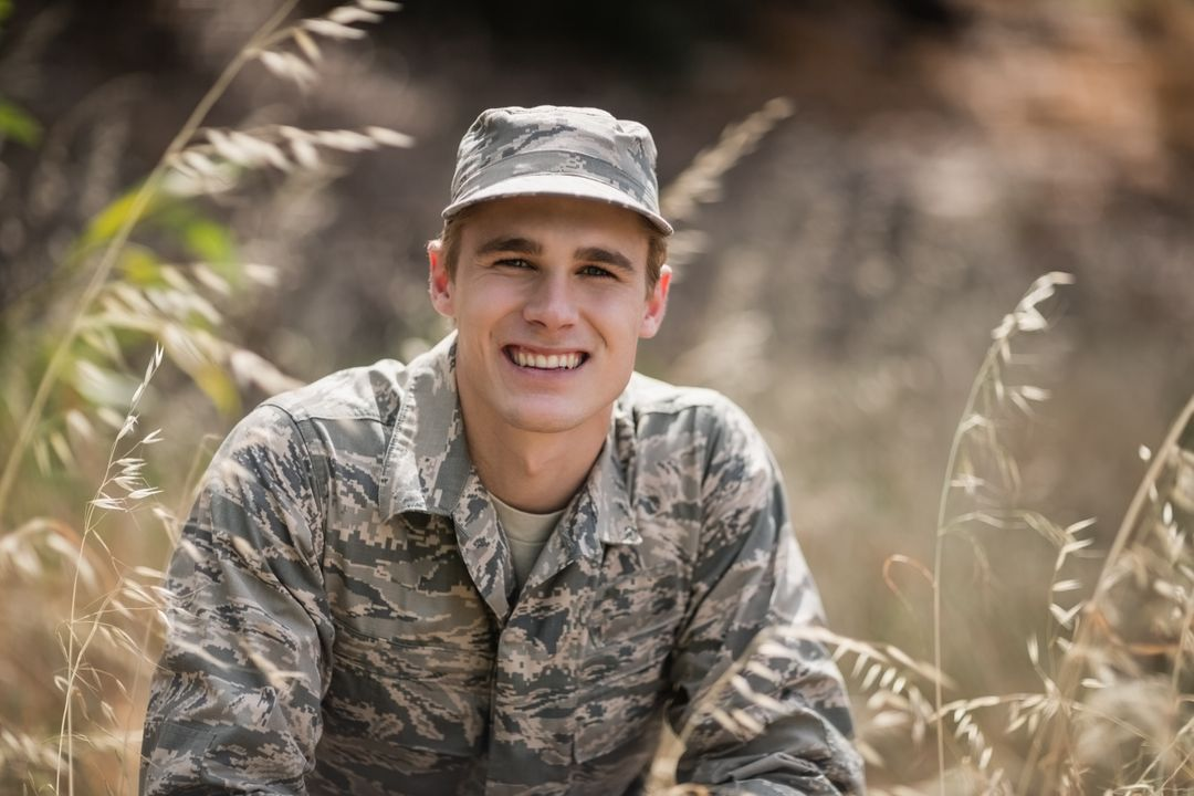 Portrait of happy military soldier crouching in grass in boot camp Free Stock Images from PikWizard