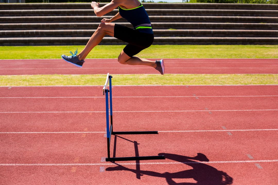 Female athlete jumping above the hurdle during the race Free Stock Images from PikWizard