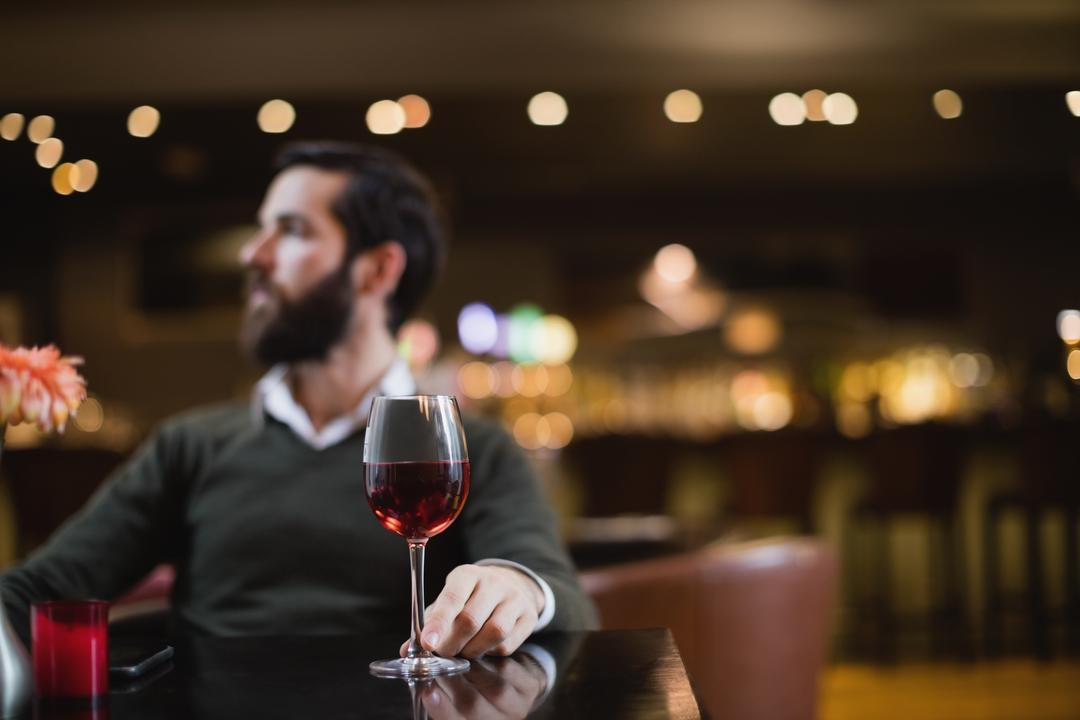 Man sitting with glass of wine in bar Free Stock Images from PikWizard