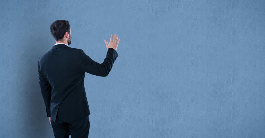 Rear view of businessman gesturing against wall