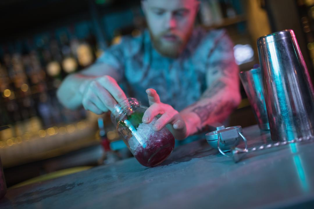 Bartender preparing cocktail at counter in bar