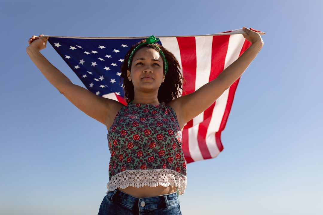 Low angle view of beautiful young Mixed-race woman waving american flag on beach in the sunshine Free Stock Images from PikWizard