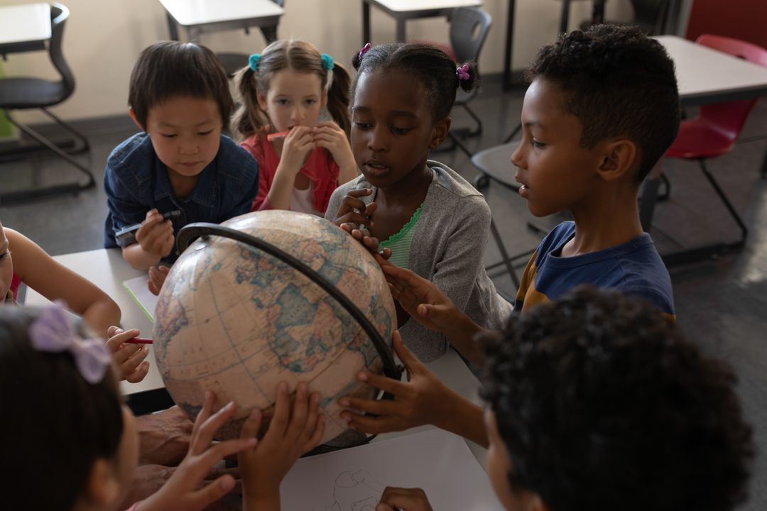 Group of kids studying a globe together in classroom of elementary school Free Stock Images from PikWizard