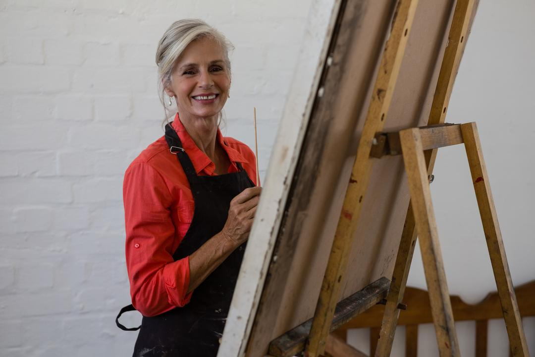 Portrait of smiling senior artist painting while standing by wall in art class Free Stock Images from PikWizard
