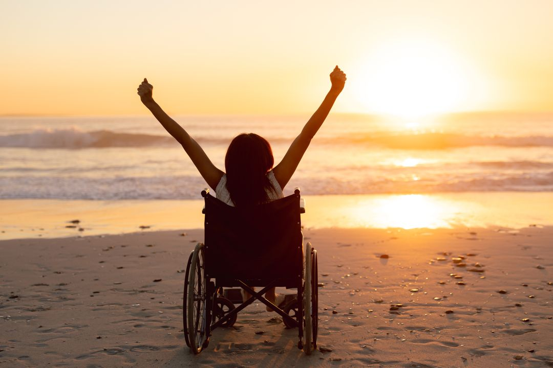 Rear view of disabled woman with arms up on the beach